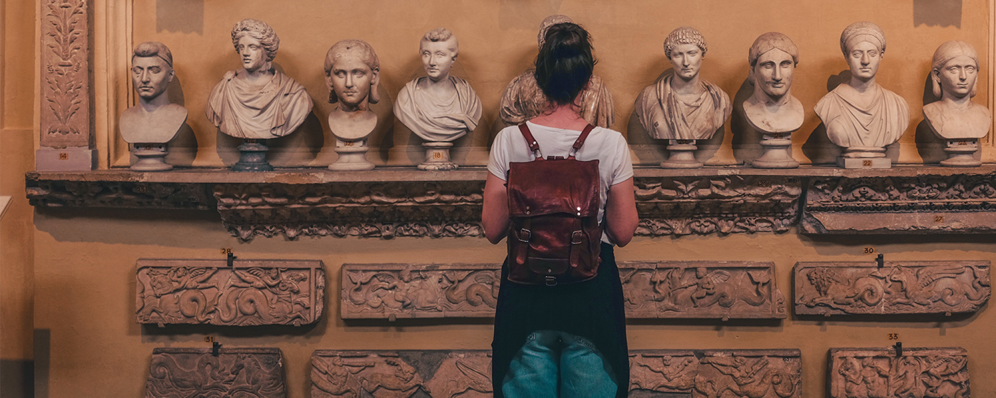 Female student examining stone busts in a museum